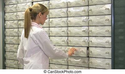 Pharmacist taking medicine from drawer. 30 fps.