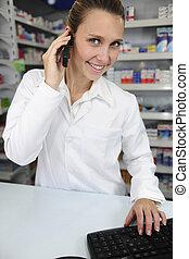 pharmacist using computer and telephone