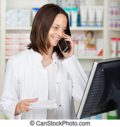 Pharmacist Using Cordless Phone While Looking At Computer