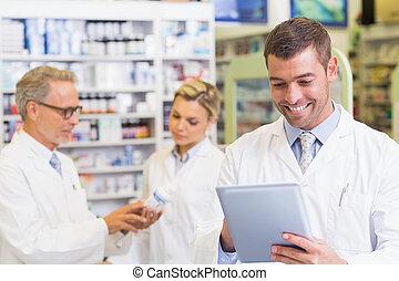 Pharmacist using the tablet at the hospital pharmacy