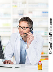 Pharmacist Wearing Headset While Using Computer At Counter