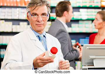Pharmacist with customers in pharmacy, he is holding a...