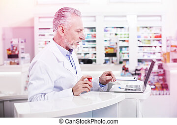 Elder grey-haired pharmacist working with a laptop