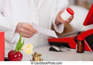 pharmacist with medicine bottle and prescription