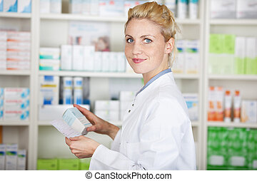 Pharmacist With Prescription At Drugstore