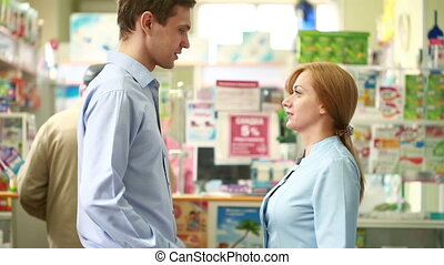 Pharmacist woman offers the visitor a cure at the chemists shop