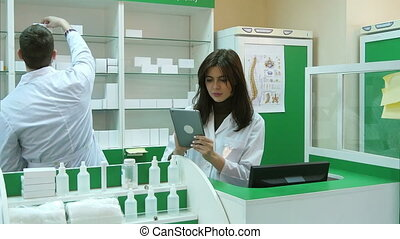 Pharmacist working with a tablet in the pharmacy holding it in her hand while reading information