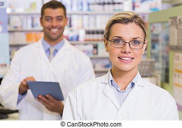 Pharmacists looking at camera at hospital pharmacy
