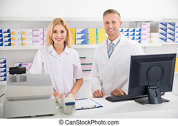 Pharmacists Smiling At Counter In Pharmacy