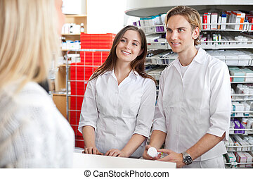 Pharmacists with Customer in Store - Two pharmacists...
