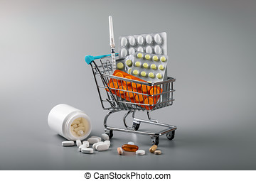 pharmacy business - shopping cart of pills on gray background