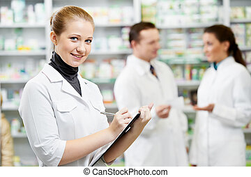 Female happy pharmacist chemist woman standing in pharmacy drugstorewit her colleagues