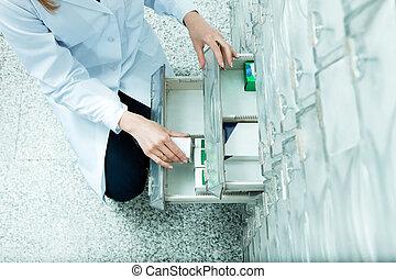 pharmacy - high angle view of pharmacist taking medicine ...