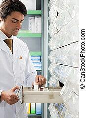 pharmacy - pharmacist taking medicine from drawer. Copy...