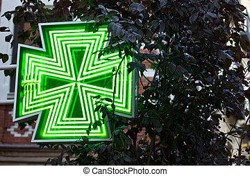 Pharmacy sign on light - A green-lit pharmacy sign in Madrid