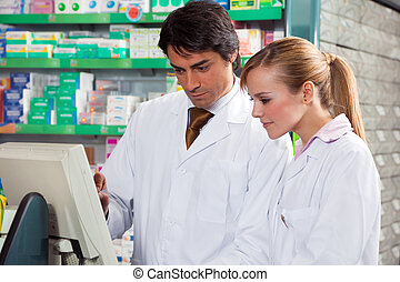 pharmacy - portrait of two pharmacists looking at computer...
