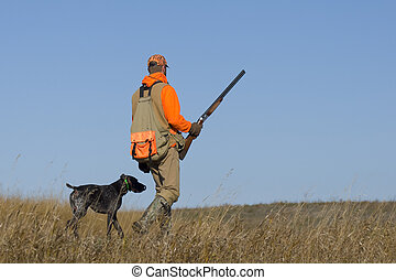 A pheasant hunter out on the prairie with his dog.