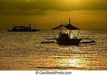 Philippine tourist boat sails on the sea at sunset.