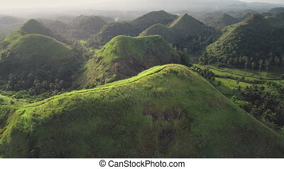 Philippines hilly countryside aerial: misty haze over mountain ranges with tropical jungle forest. Rural Asia landscape with green grass lawns, meadows and path. Nature scenery at foggy summer day