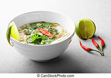 Pho bo soup with lime and chili over the gray surface