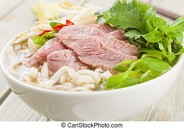 Pho Bo - Vietnamese fresh rice noodle soup with beef, herbs and chilli. Vietnam's national dish.