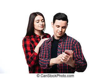 Woman hugs man that looking on smartphone screen