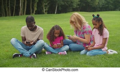 Multiracial family with cute elementary age mixed race daughters smartphone addicted sitting on green grass, ignoring each other, chatting online, browsing social media content in nature.