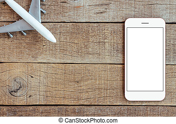 phone and airplane toy on wood table transport business concept top view, mock up phone blank screen