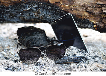 phone and sunglasses in the ashes of a bonfire, charred logs
