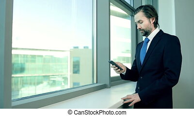 Phone Call - Businessman making a phonecall standing at the...