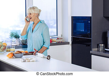 Delighted cheerful woman doing a phone call