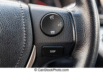 "Phone control buttons via bluetooth on the steering wheel of a car close-up, the system ""hands-free"" gadget for driver safety, equipment for switching by voice. Auto service Industry."