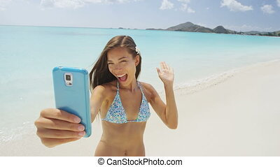 Phone girl using smartphone on beach waving hand saying hello hi on video chat having fun on beach vacation on summer travel holidays taking a selfie video. Sexy young bikini woman posing for camera.