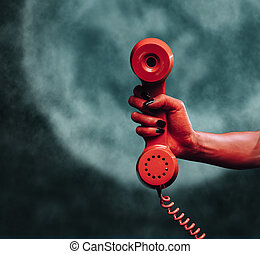 Phone handset at midnight - Red devil hand gives phone...