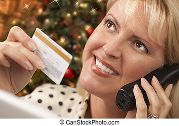 Phone Holding Woman Credit Card In Front of Christmas Tree