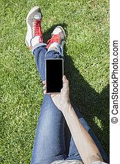 phone in hand legged on grass
