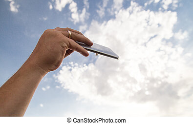 phone in hand on a background of clouds