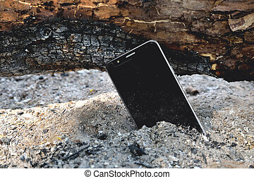 phone in the ashes of a firewood firewood dust side sun made charred log