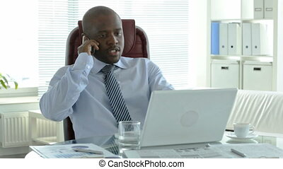 Phone negotiations - African businessman talking on the...