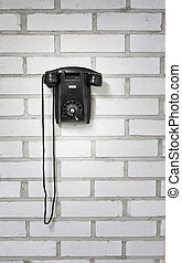 Old black phone hanging on a brick wall