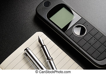 Contact us - Phone, pen, notepad. Contact us concept