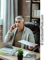 Pleasant good looking man talking on the phone