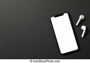 Phone with empty screen and headphones on black background, top view