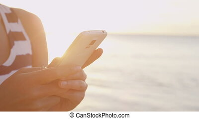 Phone - Woman sms texting using app smart phone at beach - ...
