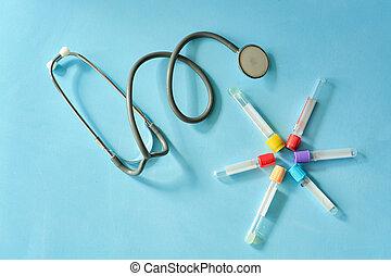 Phonendoscope stethoscope, vacuum test tubes on blue background.