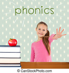 The word phonics and cute girl with hand out against red apple on pile of books