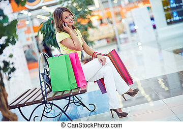 Phoning in the mall - Female shopper speaking on cellphone...