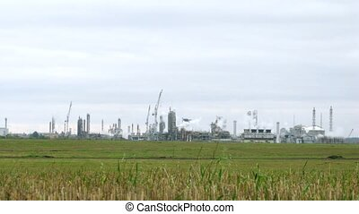Phosphoric factory stands far against blue sky, time lapse