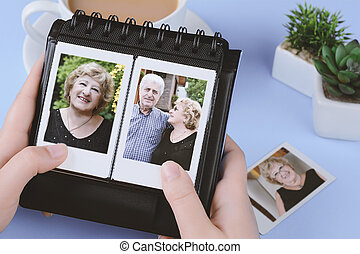 Photo album with instant photos of eldery couple