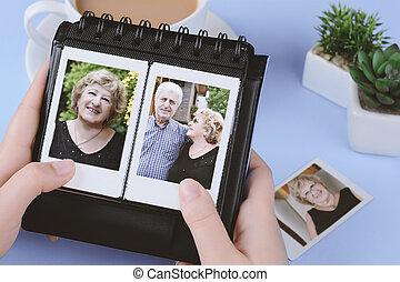 Photo album with instant photos of eldery couple